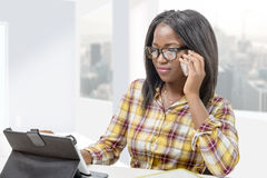 Young afro american businesswoman using tablet and giving a call Royalty Free Stock Image