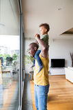 Young afro-american father with his little daughter at home. Young afro-american father at home at the window carrying his little daughter on his shoulders Royalty Free Stock Photos