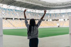 Young afro-american girl is raising the hands up while going to the stadium. Back view Royalty Free Stock Photography