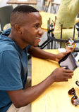 Young afro american guy at cafe with a digital tablet. Side portrait of young afro american guy sitting at outdoor cafe with a digital tablet Stock Image