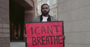Young afro american guy holding placard with i cant breath writing. Male protestor supporting movement against police