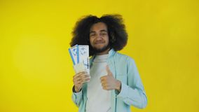 Young Afro-American man with boarding pass tickets on yellow background. 4K stock video