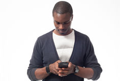 Young afro-american man looking his mobile phone. Isolated on white Royalty Free Stock Photography