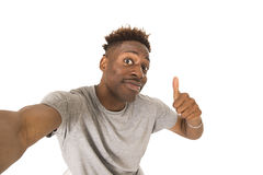 Young afro american man smiling happy taking selfie self portrait picture with mobile phone Stock Images