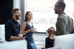 Young afro american man speaking to two of his colleagues Royalty Free Stock Photos