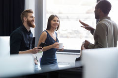 Young afro american man speaking to two of his colleagues Royalty Free Stock Image