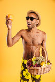 Young afro american man in swimwear holding fruit basket. Young afro american man holding fruit basket  on a orange background Stock Photography