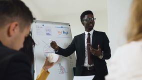 Young afro-american manager of company presenting new plan for project for team explaining business strategy using