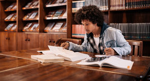 Young afro american student preparing for exam. Young afro american student preparing for the exam in the library. College student studying in the library Royalty Free Stock Photography
