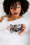 Young afro-american teen girl laying in bath with foam, wearing swag jewelry flawless, making selfie Stock Photography