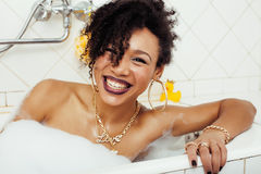 Young afro-american teen girl laying in bath with foam, wearing swag jewelry flawless, making selfie, modern lifestyle stock photography