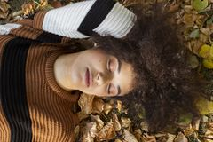Young afro american woman lying on autumnal leaves in sunny park. stock images
