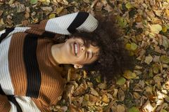 Young afro american woman lying on autumnal leaves in sunny park. stock image