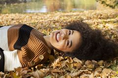 Young afro american woman lying on autumnal leaves in sunny park. royalty free stock photo
