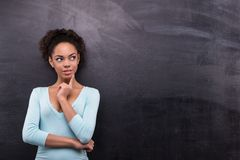 Young afro-american woman is near chalkboard Royalty Free Stock Images