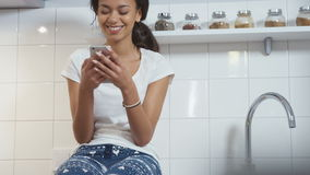 Young Afro American woman sitting in a kitchen and typing on mobile phone. stock video
