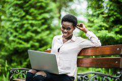 Young beauty afro american woman sitting on wooden bench in the park and working on laptop royalty free stock images