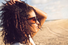 Young afro american woman in sunglasses enjoying sun. Side view portrait of a young afro american woman in sunglasses enjoying sun on a beach Royalty Free Stock Image
