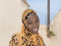 Young Afro beauty wearing a headscarf in the street and smiling royalty free stock images