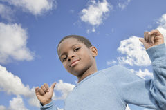 Young Afro boy, blue sky and sunny day Stock Photos