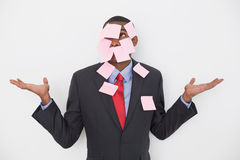Young Afro businessman covered in blank notes Royalty Free Stock Image