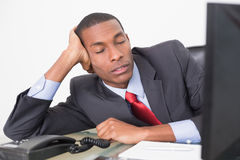 Young Afro businessman resting at desk Stock Image