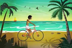Young afro woman rides red bike on summer beach at sunset Royalty Free Stock Photos