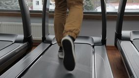 Young afroamerican man runs along treadmill in sports club. Guy jogs on aerobic equipment, which imitates running track, with moving magnetic tape stock footage
