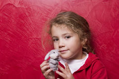 Young age. Little girl showing her toy Stock Image