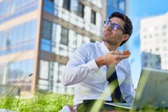 Eating by work. Young agent in shirt and tie going to have slice of pizza while looking at sun on the sky in urban environment Royalty Free Stock Photo