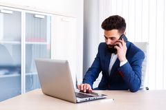 Young Agent Talking On Phone While Works On Laptop. Young Business Man Working On Laptop At Office - Workplace Stock Photography