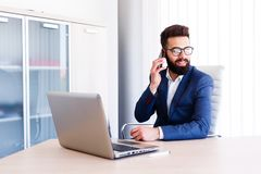 Young Agent Talking On Phone While Works On Laptop. Young Business Man Working On Laptop At Office - Workplace Stock Photo