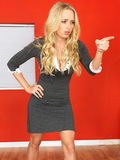 Young Aggressive Agitated Cross Angry Woman Standing Pointing. A DSLR royalty free image, of young professional business woman secretary boss, standing pointing Royalty Free Stock Photography