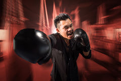 Young aggressive businessman training shadow boxing at gym Stock Image