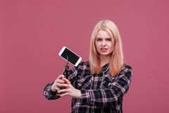 Aggressive girl angrily squeezed the modern mobile phone with a plugged screen. Pink background. Stock Photo