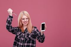 Aggressive girl holds a smartphone and angrily flaunts it with a screwdriver. On a pink background. Stock Images