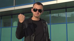Young aggressive man in leather jacket and sunglasses showing a fist and standing outdoor.  stock video footage