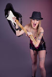 Young aggressive woman with tattoo smashing guitar Stock Photography
