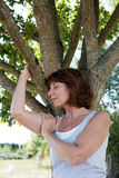 Young aging woman in meditation with a tree for revitalization Stock Images