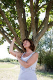 Young aging woman in reflection with a tree for revitalization Royalty Free Stock Photography