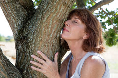 Young aging woman smelling a tree for natural memories. Senior green wellness - smiling mature woman embracing a tree in harmony with nature seeking for woody stock image
