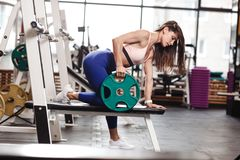 Young ahletic brunette girl dressed in a sportswear is doing exercises for back with plate on the bench in the modern royalty free stock image