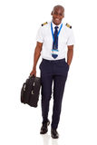 Young airline pilot. Happy young airline pilot carrying briefcase isolated on white background stock image