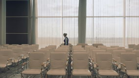 Young airport employee in the conference hall checks the room. The camera moves from the right to the left. Young beautiful blonde wearing the uniform goes stock video