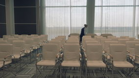Young airport worker in the conference hall checks the room. The camera moves from the right to the left. Young beautiful blonde wearing the uniform goes across stock video footage