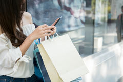 Young aisin woman using her smartphone and hold shopping bag. Young aisin woman using her smartphone and hold shopping bag while doing some shopping in a street Stock Images