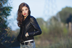 Young alarmed beautiful woman with bright trendy makeup wavy hairstyle in black leather jacket  and blue jeans strolling in the pa Royalty Free Stock Photo