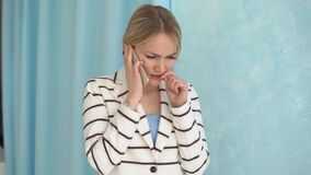 Young alarmed woman in a striped jacket talking on the phone.  stock footage