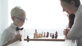 A young albino playing with his mother in chess. They are dressed in white shirts. Move the chess pieces