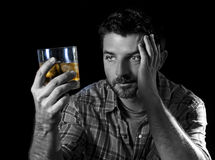 Young alcoholic addict man drunk with whiskey glass in alcoholism concept. Young alcoholic wasted man drunk looking at whiskey glass thinking and feeling royalty free stock images